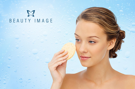 Young Woman Cleaning her Face with Exfoliating Sponge